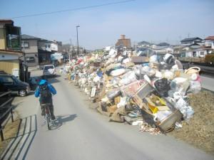 家屋から搬出され道脇に積まれた廃棄物の山